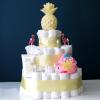 Ronde luiertaart met drie lagen. elke laag is versierd met geel satijnen lint. De taart is versierd met roze zwemluier, zonnebrand van Naïf, twee flamingo prikkers, geel ananas nachtlampje op de top en baby wattenstaafjes.