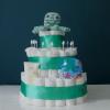 luiertaart met drie lagen, elke laag heeft een versiering van donkergroen satijnen lint. De cadeautjes die je ziet op de taart zijn: een octopus rammelaar met groene, blauwe en witte horizontale strepen, zonnebrand van het merk Naïf, blauwe zwemluier. In de luiertaart zitten twee hydrofiel doeken met cactusjes