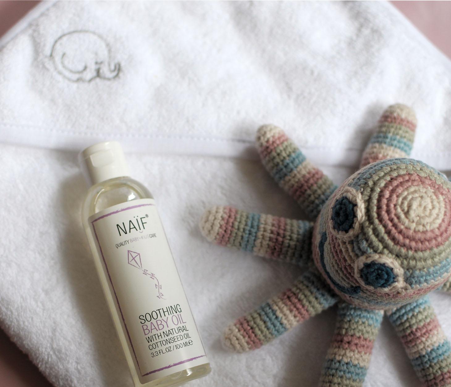 Affbeelding met op de achtergrond een witte handdoek met een klein grijs olifantje rechts bovenin. Links een flesje van Naif baby olie. Rechtsonder een octopus rammelaar, gehaakt met pastel kleuren: wit, roze, groen en blauw gestreept