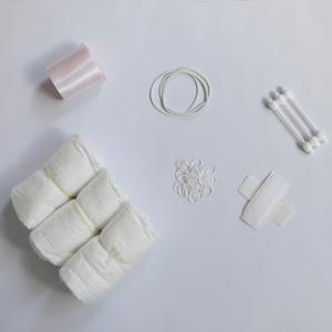 Witte achtergrond, links boven roze satijn lint, links onder drie witte luiers, midden boven drie witte grote elastieken, midden onder kleine elastiekjes, rechts boven drie baby wattenstaafjes, rechts onder zelfklevend klittenband neergelegd in een kruisje