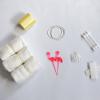 Witte achtergrond, links boven geel satijn lint, links onder drie witte luiers, midden boven drie witte grote elastieken, midden onder kleine elastiekjes en twee roze flamingo prikkers, rechts boven drie baby wattenstaafjes, rechts onder zelfklevend klittenband neergelegd in een kruisje