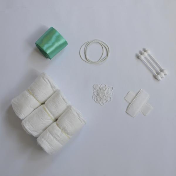 Witte achtergrond, links boven groen satijn lint, links onder drie witte luiers, midden boven drie witte grote elastieken, midden onder kleine elastiekjes, rechts boven drie baby wattenstaafjes, rechts onder zelfklevend klittenband neergelegd in een kruisje