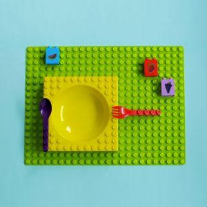 Groene duplo placemat met geel Duplo ontbijtbordje, paarse Duplo lepel, rode Duplo vork, Duplo leersteen in de kleur blauw met een afbeelding van een meloen, Duplo leersteen in de kleur rood met een afbeelding van een aardbei, Duplo leersteen in de kleur paars met een afbeelding van een tros druiven