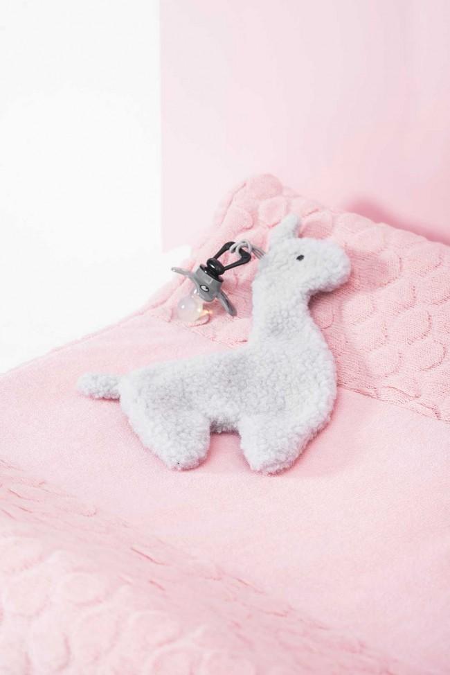Speendoekje in de vorm van een lama, grijze kleur. Het speendoekje ligt op een roze kleed en er zit een speen aan vast.