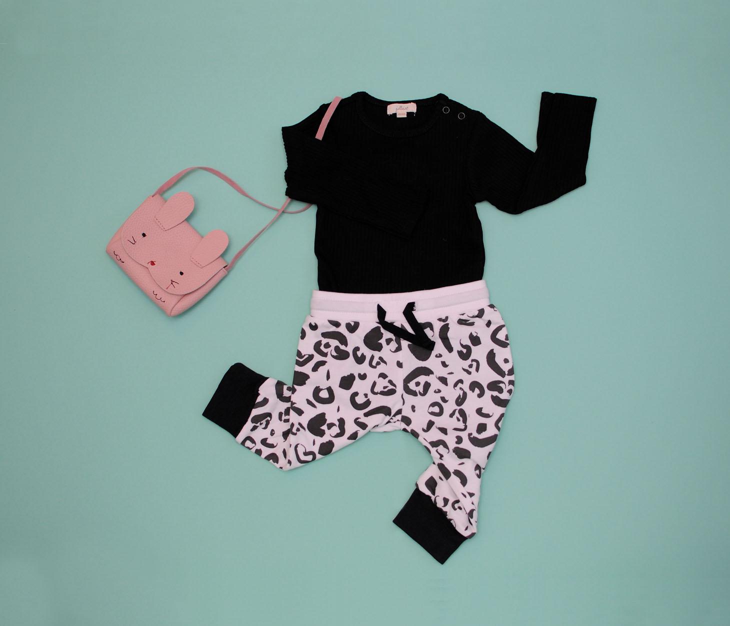 Groene achtergrond zwarte romper en broekje met zwart wit luipaard print. konijnentasje in de kleur pastel roze