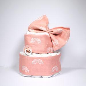Lieve luiertaart bedekt met zacht roze hydrofieldoeken met een regenboog print