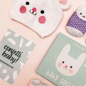 Brievenbus kraamcadeau konijnen muts en konijnen sokjes in vier verschillende kleurtjes (paars, groen, blauw, roze) en een kaartje confetti baby
